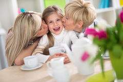 Sweet girl receiving kiss from her family Royalty Free Stock Images
