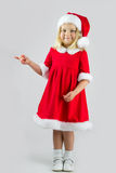 Sweet girl in a red Christmas costume. Standing in a studio and pointing at something royalty free stock photography