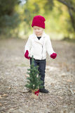 Sweet Girl In Red Mittens and Cap Near Small Christmas Tree Stock Photos