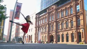 Sweet girl in a red skirt dances and turns in the afternoon near a shopping center in the square, slow motion stock footage
