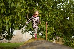 Sweet girl running along a stone fence. Holidays in the countryside, vacations in nature stock photography