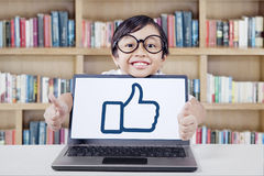 Sweet girl showing OK symbol with laptop. Happy little girl smiling on the camera while showing hands gesture and a thumb up symbol on the laptop screen, shot in Royalty Free Stock Photos