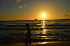 Sweet girl silhouette tending to the waves against the Sunset Royalty Free Stock Photo