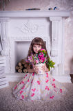 Sweet girl sitting with a bunch of flowers Royalty Free Stock Photos