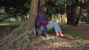 Sweet girl with a smartphone is sitting under a tree with mighty winding roots stock video footage