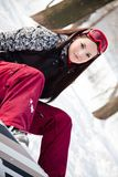 Sweet girl with snowboard sits on snow Royalty Free Stock Photography