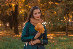 Sweet girl stands in autumn Park looks Afar and keeps the leaves in hand Royalty Free Stock Images