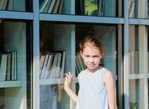 A sweet girl stands with her back to a book glass window stock images
