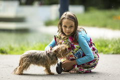 Sweet  girl on the street with a small dog. Stock Image