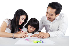 Sweet girl studying with her parents Royalty Free Stock Images