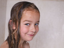 Sweet girl taking a shower. 3 year old girl with wet hair and face from taking a bath Stock Image