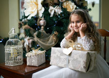 Sweet girl thought sitting with  gift near  Christmas tree Royalty Free Stock Photos