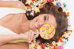 Sweet girl. Top view of beautiful young women holding a lollipop Royalty Free Stock Photos