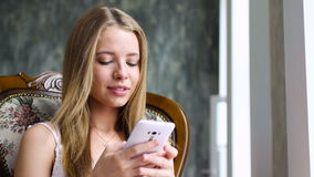 Sweet girl typing message on smartphone stock video footage