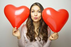 Sweet girl with Valentine heart balloons looking at the camera and making air kiss. Lovely young woman with two heart shaped balloons on white background Royalty Free Stock Images