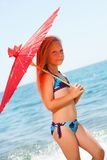 Sweet girl walking with umbrella on beach. Royalty Free Stock Image