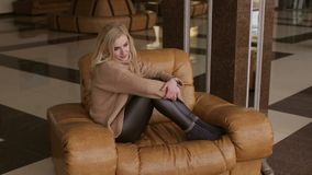 Portrait of a girl resting in a chair in a hotel. stock video footage