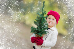 Sweet Girl Wearing Mittens Holding Small Christmas Tree with Snow Effe Royalty Free Stock Images