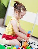 Sweet girl who build towers with plastic cubes Stock Images