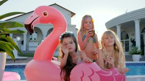 Sweet girls lie on inflatable pink flamingo near pool, spoiled rich childs in backlight outdoors, children have fun stock video