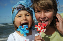 Sweet girls with lollipop. Sweet girls with puzzle lollipop on the beach stock images