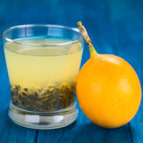 Sweet Granadilla Juice. Fresh juice made of sweet granadilla or grenadia (lat. Passiflora ligularis) with its seeds in glass, granadilla fruit on the side ( Stock Image