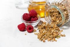 Sweet granola in a jar, fresh raspberries and honey, closeup. Horizontal Stock Photo