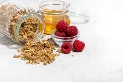 Sweet granola in a jar, fresh raspberries and honey. On white table, closeup horizontal Royalty Free Stock Photo