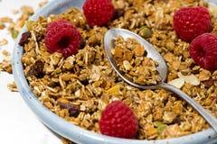 Sweet granola on the plate and fresh raspberries. Closeup Stock Photos