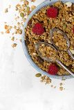 Sweet granola on the plate and fresh raspberries on white table. Closeup Stock Photography