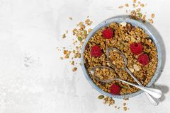 Sweet granola on the plate and fresh raspberries on white table. Top view horizontal Stock Photos