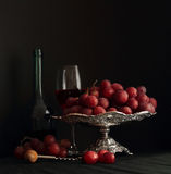 Sweet grapes on silver tray and glass of wine Royalty Free Stock Photography