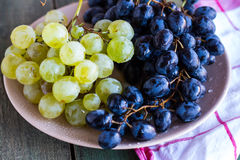 Sweet green and blue grapes on a plate, closeup Royalty Free Stock Images