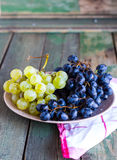 Sweet green and blue grapes on a plate Royalty Free Stock Photo