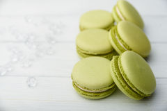 Sweet green macaroons on wooden table Stock Photos