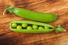 Sweet green peas. Sweet green peas on an old wooden background Stock Photos