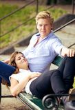 Sweet Guy with Girlfriend Resting on His Lap. Portrait of a sweet guy together with his girlfriend resting on his lap on a park bench stock images