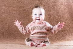 Sweet happy baby girl on a brown blanket Royalty Free Stock Image
