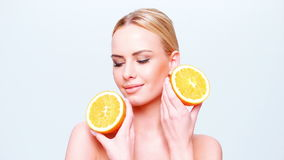 Sweet and Happy Blond Girl Holding Orange Fruit Royalty Free Stock Photography