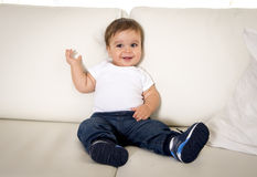 Sweet happy little baby boy lying alone on sofa at home in small jeans and sneakers. Candid portrait of sweet happy little baby boy lying alone on sofa couch at Royalty Free Stock Photos