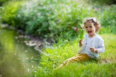Sweet, happy little girl sitting on grass. Sweet, happy little girl sitting on a grass in a park at a spring stream with flower in hand. Laughing, enjoying fresh royalty free stock photos