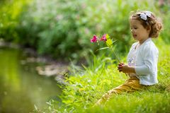 Sweet, happy little girl sitting on grass. Sweet, happy little girl sitting on a grass in a park at a spring stream with flower in hand. Laughing, enjoying fresh royalty free stock image