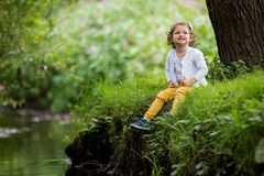 Sweet, happy little girl sitting on grass. Sweet, happy little girl sitting on a grass in a park at a spring stream with flower in hand. Laughing, enjoying fresh Royalty Free Stock Images