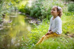 Sweet, happy little girl sitting on grass. Sweet, happy little girl sitting on a grass in a park at a spring stream with flower in hand. Laughing, enjoying fresh Stock Photos