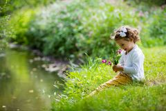 Sweet, happy little girl sitting on grass. Sweet, happy little girl sitting on a grass in a park at a spring stream with flower in hand. Laughing, enjoying fresh royalty free stock photography