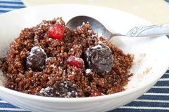 Healthy dessert from boiled quinoa with dried fruit. Sweet but healthy dessert from boiled quinoa with dried plums and cherries on white plate with spoon Stock Photography