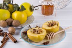 Sweet healthy dessert. Fruit quince with honey. Walnut is ready for baking royalty free stock images