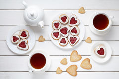 Sweet heart cookies for Valentines day with teapot and two cups of tea composition on white wooden background Royalty Free Stock Image