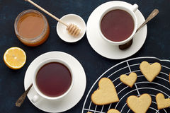 Sweet heart shaped cookies for Valentines day and two cups of tea on the table. Stock Photo