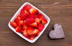 Sweet heart-shaped and strawberries on wood from above Stock Photo